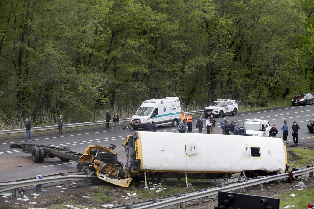 Emergency personnel work at the scene of a school bus and dump truck collision, injuring multiple people, on Interstate 80 in Mount Olive, N.J., Thursday, May 17, 2018. (Seth Wenig/AP)