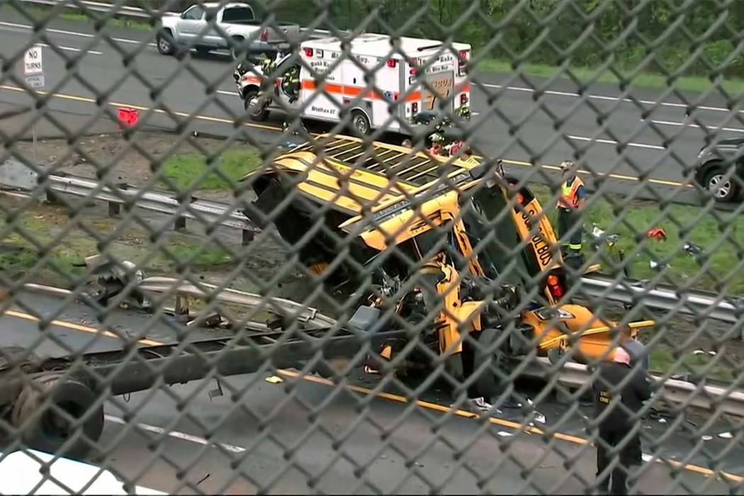 This image taken from WABC-TV video shows an overturned school bus after it collided with a dump truck, injuring multiple people, on Interstate 80 in Mount Olive, New Jersey, Thursday, May 17, 201 ...