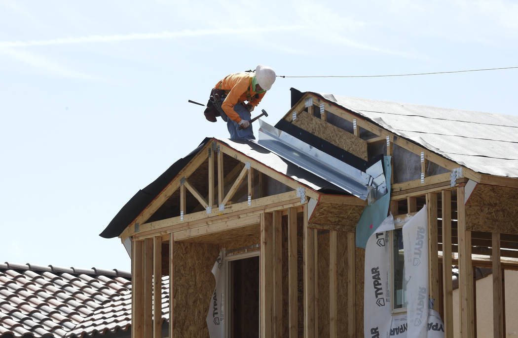 A construction worker puts a roof on a new home at the Cove at Southern Highlands and St. Rose parkways on April 18, 2018. (Bizuayehu Tesfaye Las Vegas Review-Journal)