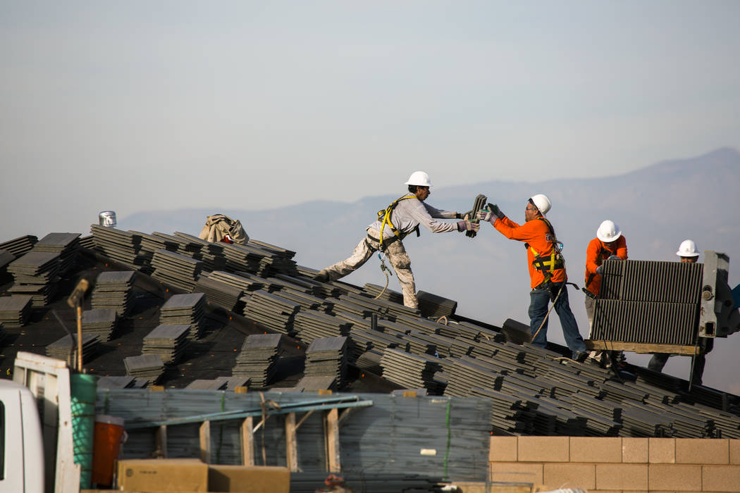 Workmen place roofing tiles on a single-family homes at Cadence in 2016. Recent local data shows that new homes priced under $300,000 are disappearing in the valley. (Las Vegas Review-Journal 2016 ...