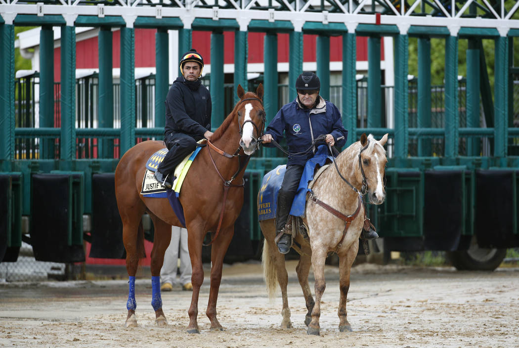 Kentucky Derby winner Justify, left, with exercise rider Humberto Gomez aboard, waits near the starting gate before being escorted to the track for a workout, Thursday, May 17, 2018, at Pimlico Ra ...