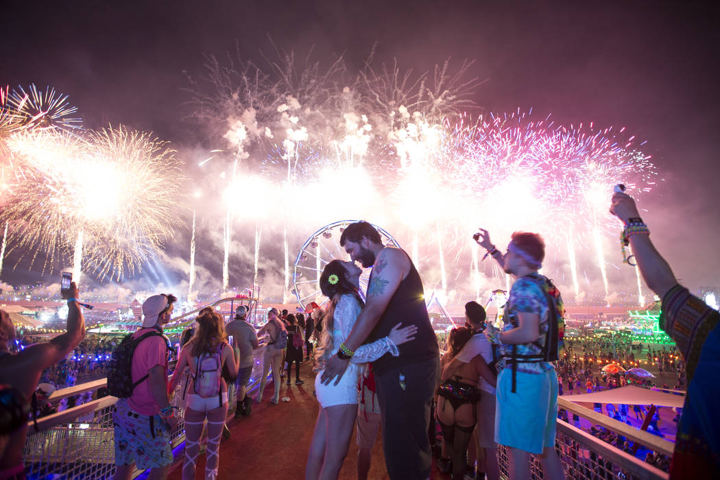 Festivalgoers Yolanda Retana, left, and Albert Robles of Los Angeles, share a kiss during a firework show on Day1 of the Electric Daisy Carnival at the Las Vegas Motor Speedway on Saturday, May 19 ...