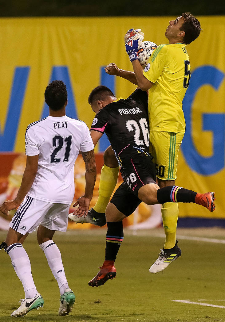 Real Monarchs goaltender Jacob Leeker (50) makes a save over Las Vegas Lights FC midfielder Julian Portugal (26) as Monarchs defender Taylor Peay (21) looks for the rebound during the second half ...
