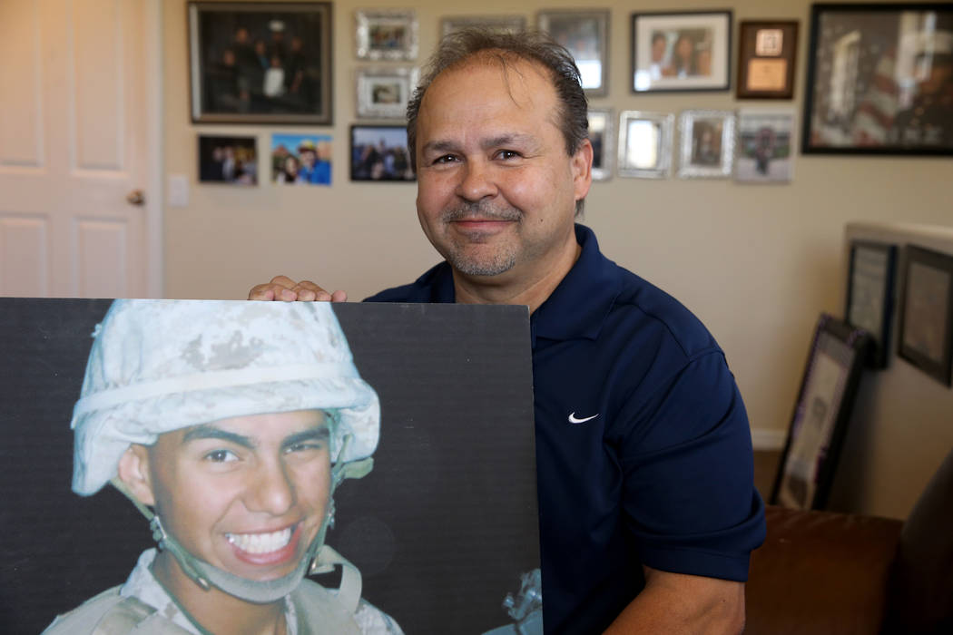 Richard Perez Sr. holds a photo of his son at his Henderson home on May 17, 2018. Richard Perez Jr. died while serving as a Marine in Iraq in 2005. The senior Perez will throw out the first pitch ...