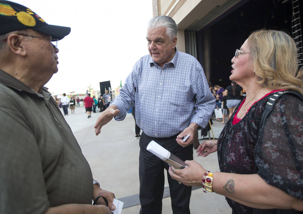 Clark County Commission Chairman and Nevada Gubernatorial candidate Steve Sisolak, center, greets Air Force veteran Vince Caguimbal and his wife, Minnie, during El Tiempo's Cinco de Mayo Fiesta at ...
