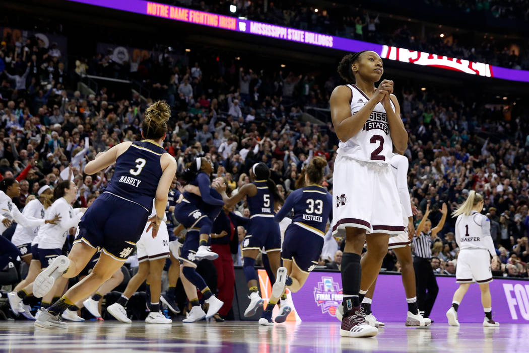 Mississippi State's Morgan William (2) pauses as Notre Dame's Arike Ogunbowale is mobbed by teammates in the background after Ogunbowale's game-winning basket at the buzzer in the final game of th ...