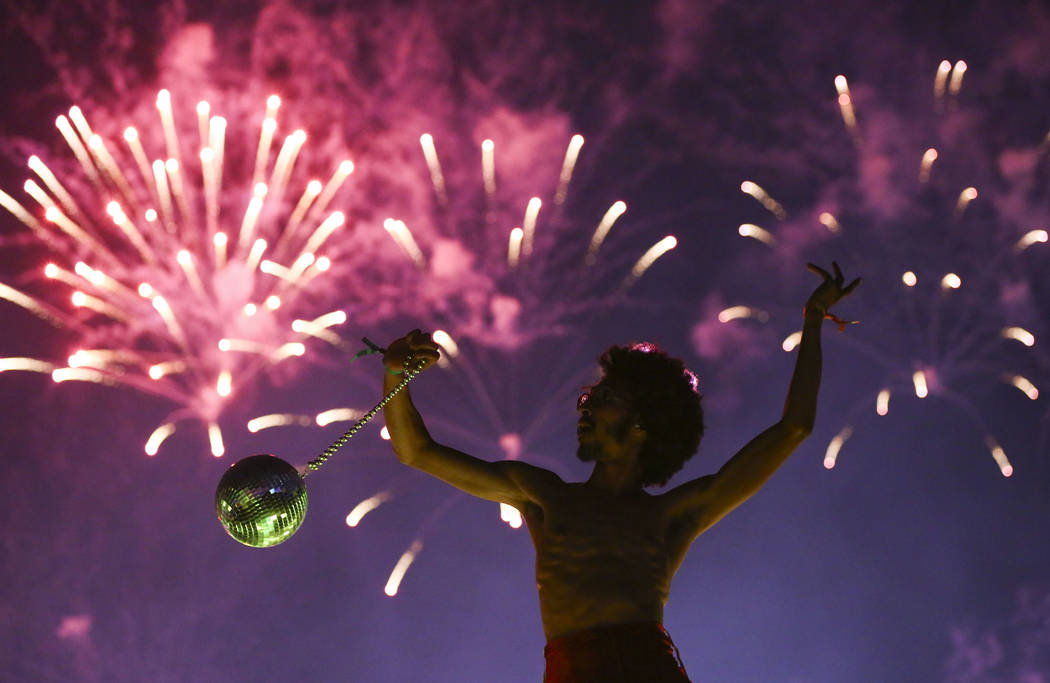 Deven Williams of the Kalliope dances on an art car as fireworks go off during the third day of the Electric Daisy Carnival at the Las Vegas Motor Speedway in Las Vegas during the early hours of M ...