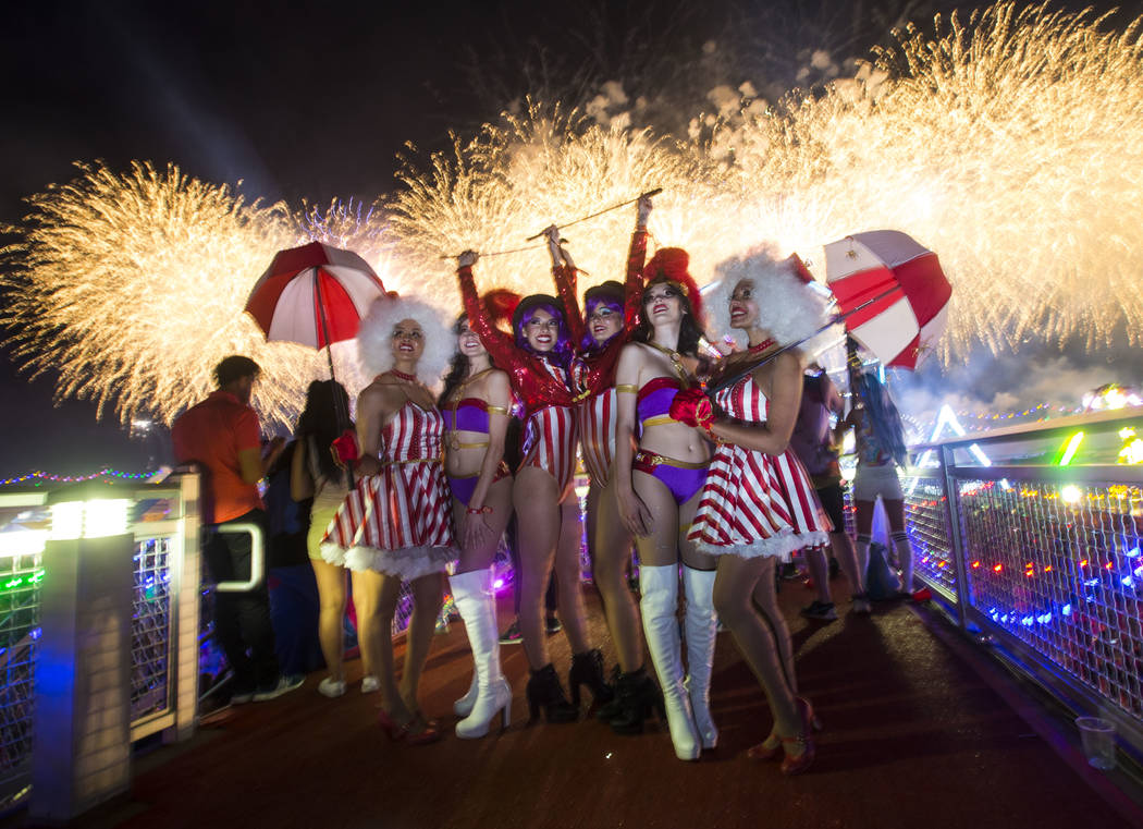 "Costumed performers, including the ""carousel girls"" and the ""ringmasters,"" pose as fireworks go off during the first day of the Electric Daisy Carnival at the Las Vegas Motor S ..."