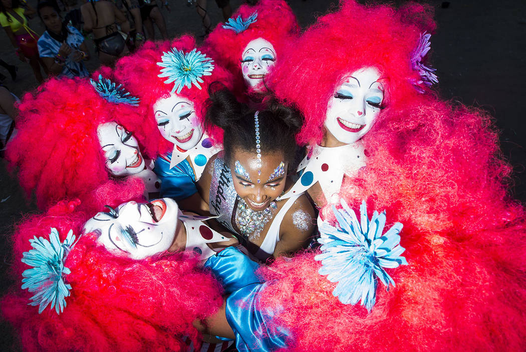 Christy Muok of New York, center, is surrounded by costumed performers during the third day of the Electric Daisy Carnival at the Las Vegas Motor Speedway in Las Vegas on Sunday, May 20, 2018. Cha ...