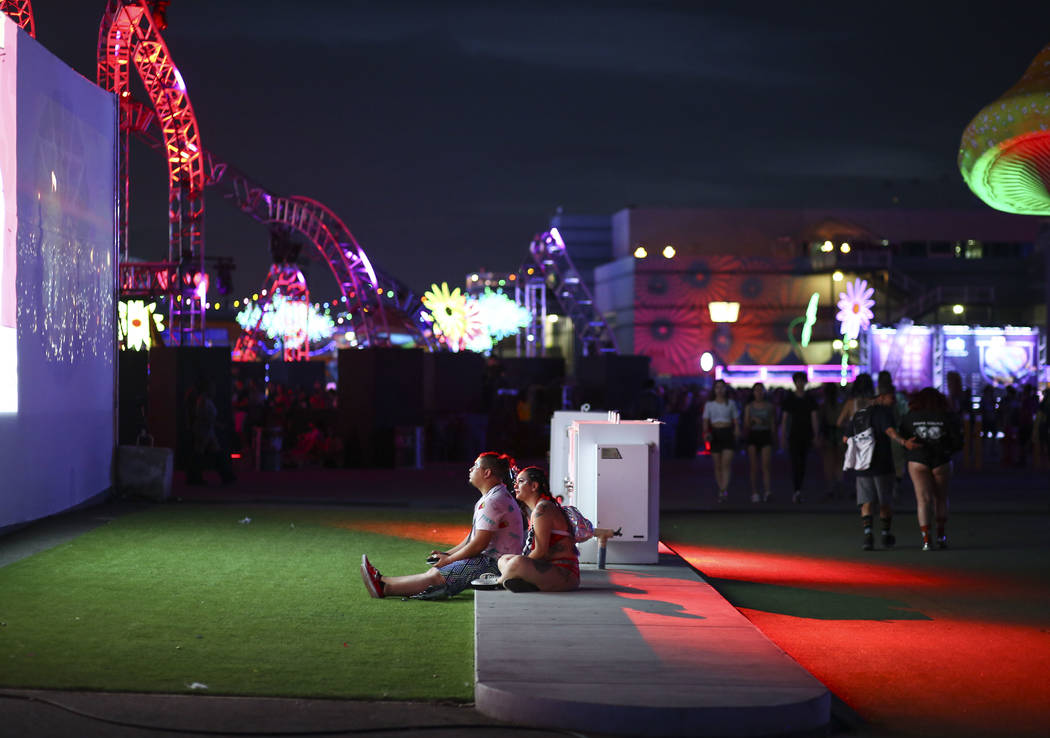 Rodger Romero, left, and Karlee Romero of Las Vegas relax while watching a display play videos during the third day of the Electric Daisy Carnival at the Las Vegas Motor Speedway in Las Vegas on S ...