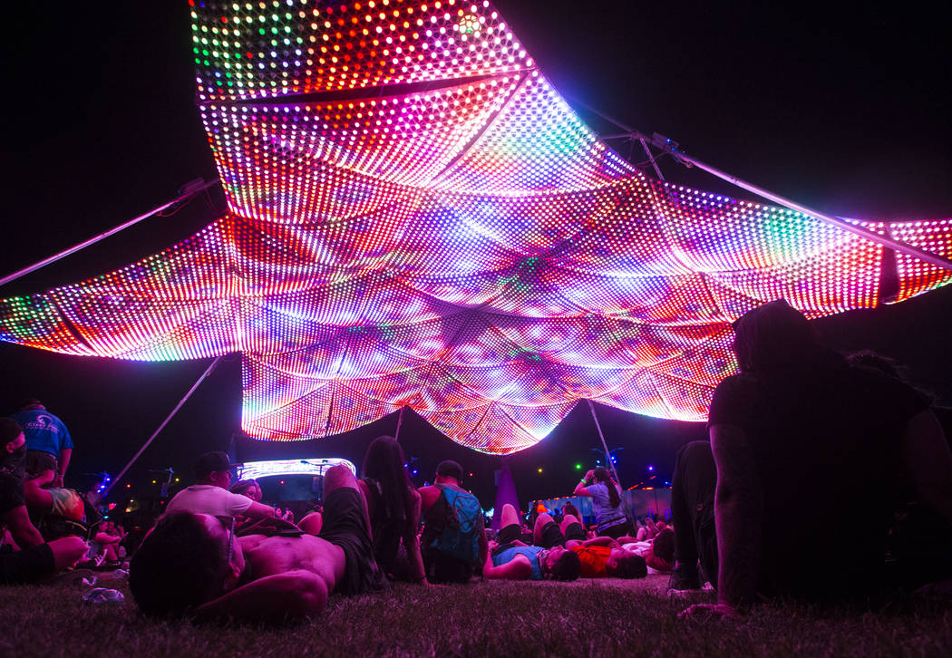 Attendees relax beneath the Firmament art installation during the third day of the Electric Daisy Carnival at the Las Vegas Motor Speedway in Las Vegas on Sunday, May 20, 2018. Chase Stevens Las V ...