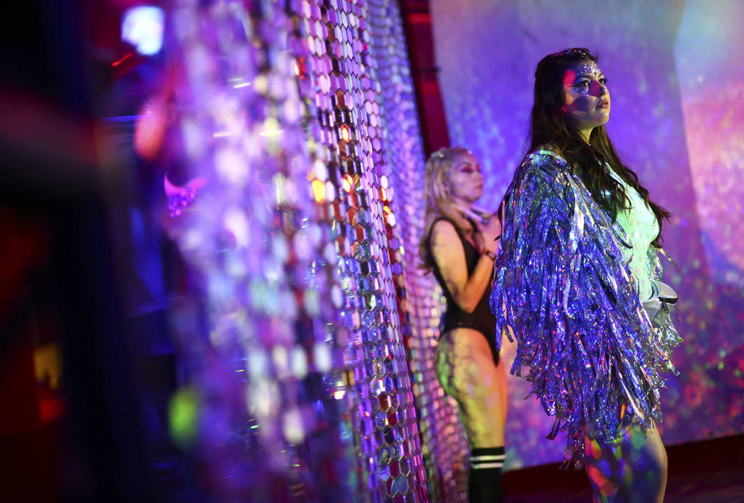 Attendees stand for photos near a reflective art installation in Carnival Square during the third day of the Electric Daisy Carnival at the Las Vegas Motor Speedway in Las Vegas on Sunday, May 20, ...