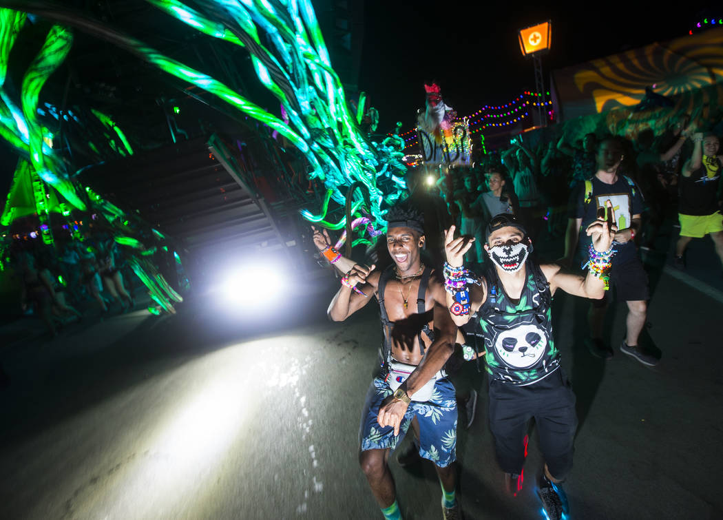 Attendees dance alongside the moving Parliament art car during the second day of the Electric Daisy Carnival at the Las Vegas Motor Speedway in Las Vegas on Saturday, May 19, 2018. Chase Stevens L ...