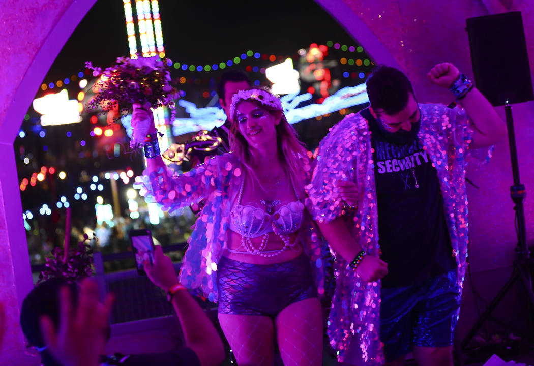 Brittany Broussard and Darren O'Connor celebrate at the conclusion of their wedding ceremony during the second day of the Electric Daisy Carnival at the Las Vegas Motor Speedway in Las Vegas on Sa ...