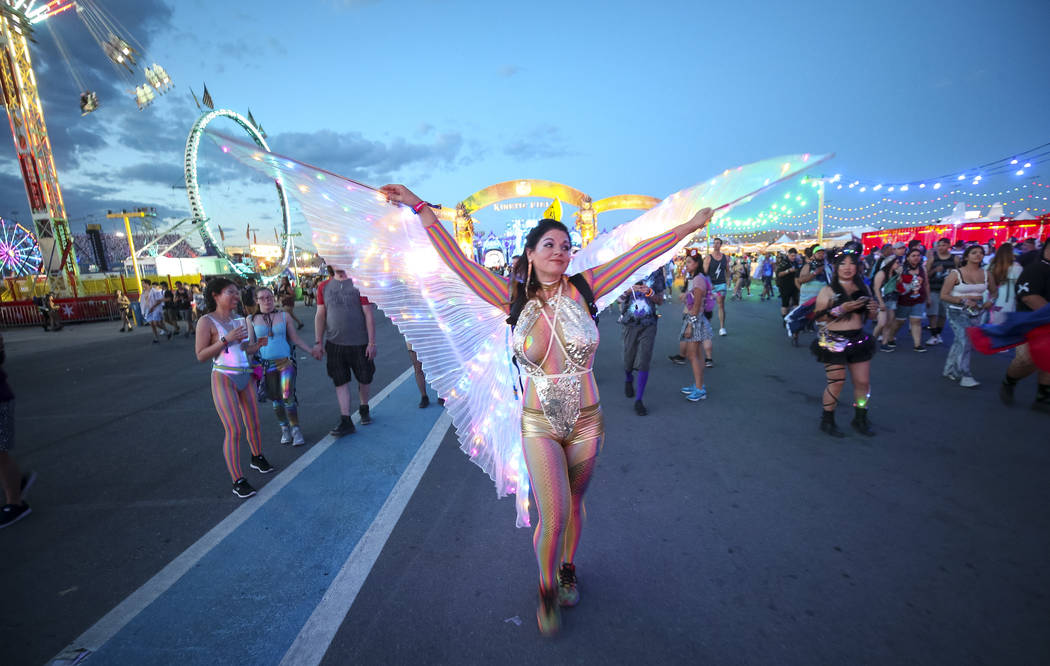 Festivalgoer Amy Lopez-Kohler of California wanders through the crowd with her illuminated wings on day one of the Electric Daisy Carnival at the Las Vegas Motor Speedway on Friday, May 18, 2018. ...