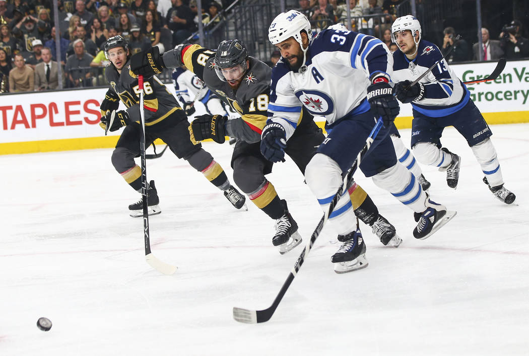 Golden Knights left wing James Neal (18) and Winnipeg Jets defenseman Dustin Byfuglien (33) chase after the puck during the first period of Game 3 of the NHL Western Conference finals hockey playo ...