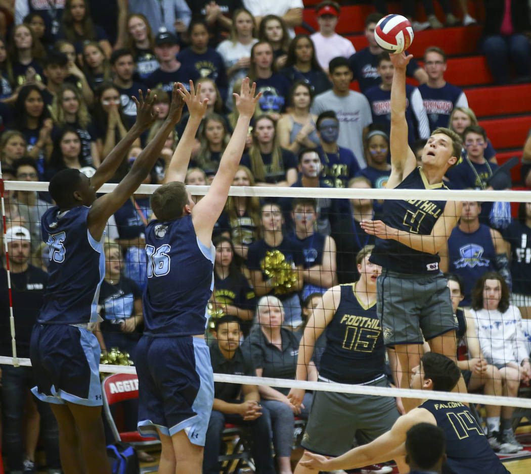 Foothill's Tanner Lester (4) sends the ball over the net as Centennial's Nahmani Brown (15) and Tyler Godown (16) defend during the first set of the Class 4A state volleyball championship match a ...
