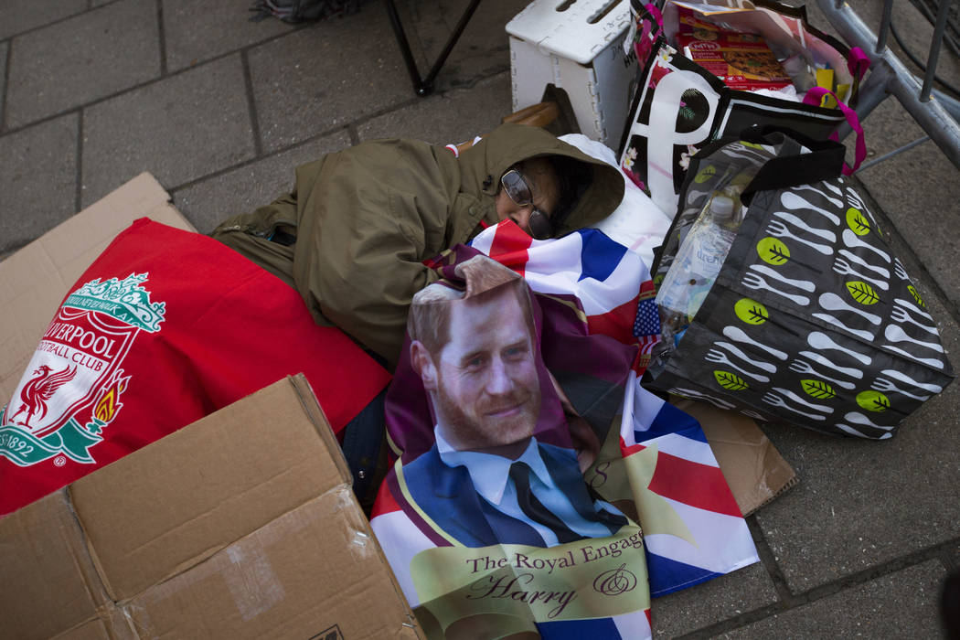 A woman sleeps on the ground in front of Windsor castle, England, Friday, May 18, 2018. Preparations continue in Windsor ahead of the royal wedding of Britain's Prince Harry and Meghan Markle Satu ...