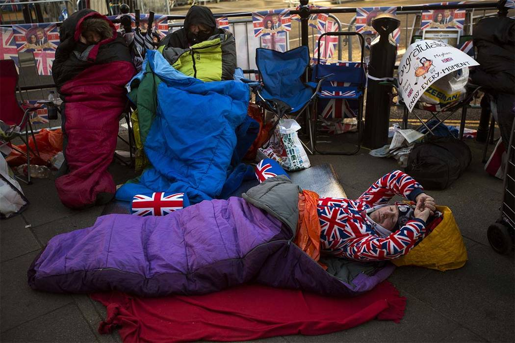 A man sleeps on the ground, spending the night near Windsor castle, England, Friday, May 18, 2018. Preparations continue in Windsor ahead of the royal wedding of Britain's Prince Harry and Meghan ...