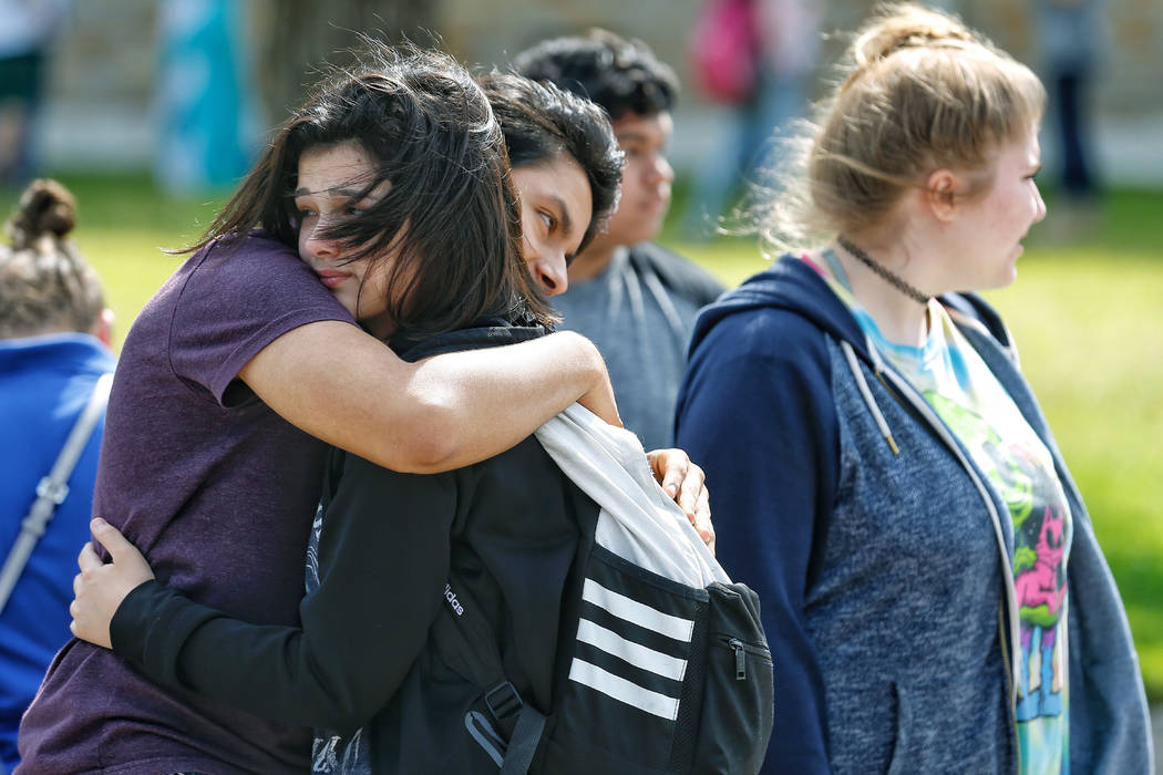 Santa Fe High School freshman Caitlyn Girouard, center, hugs her friend outside the Alamo Gym where students and parents wait to reunite following a shooting at Santa Fe High School Friday, May 18 ...