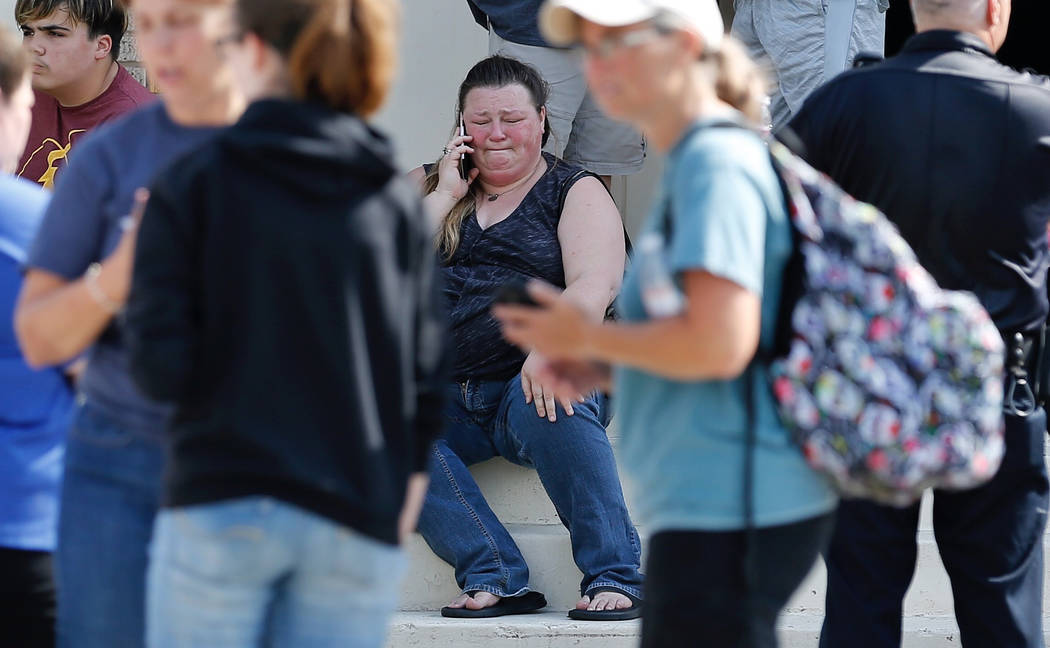 A woman reacts while making a phone call outside the Alamo Gym where parents wait to reunite with their children following a shooting at Santa Fe High School in Santa Fe, Texas, on Friday, May 18, ...