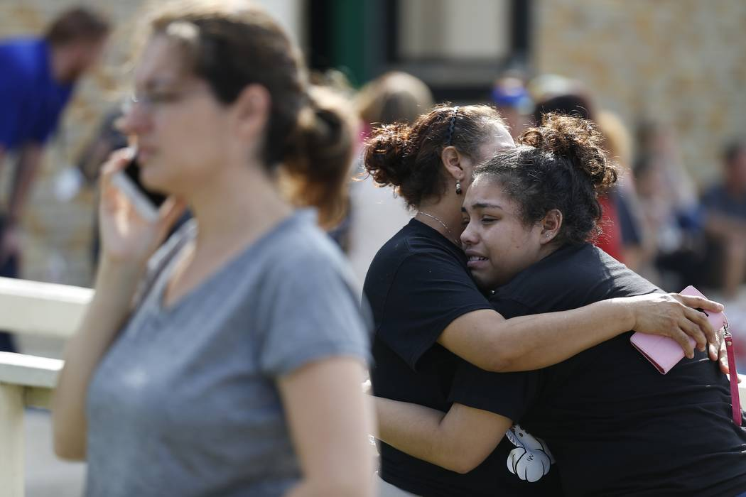 Santa Fe High School junior Guadalupe Sanchez, 16, cries in the arms of her mother, Elida Sanchez, after reuniting with her at a meeting point at a nearby Alamo Gym fitness center following a shoo ...