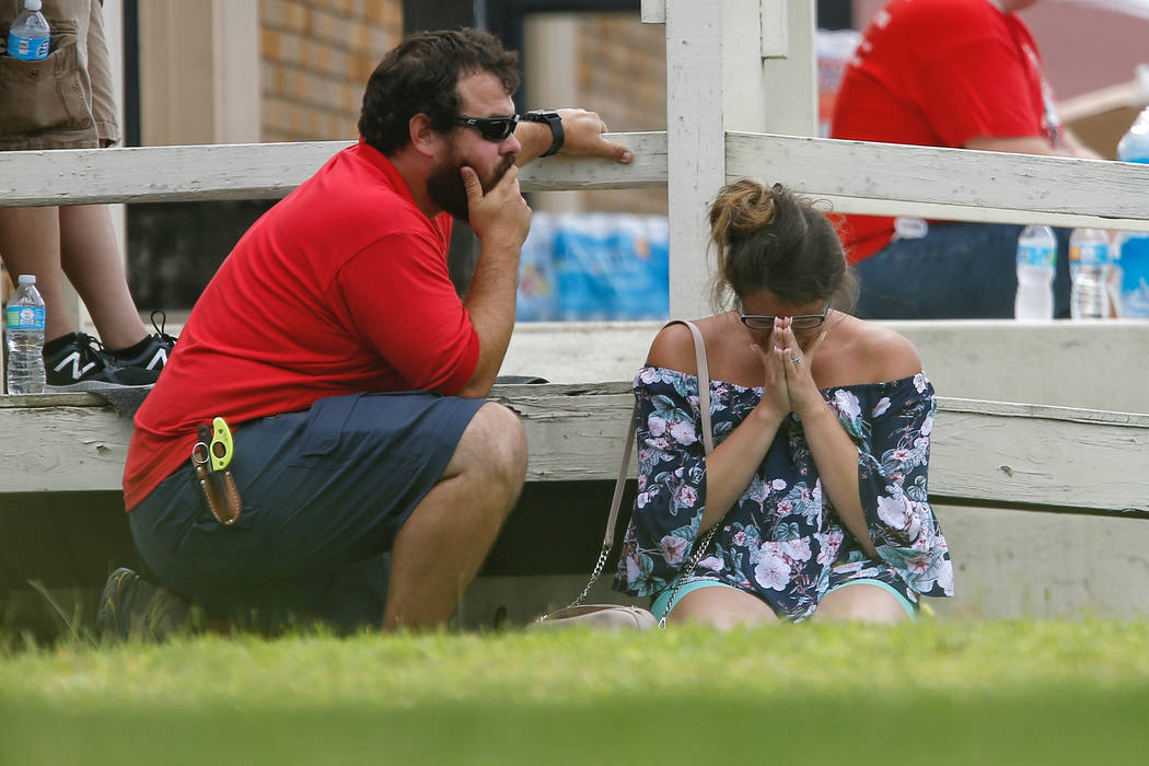 A woman prays in the grass outside the Alamo Gym where parents wait to reunite with their kids following a shooting at Santa Fe High School Friday, May 18, 2018, in Santa Fe, Texas. (Michael Ciagl ...