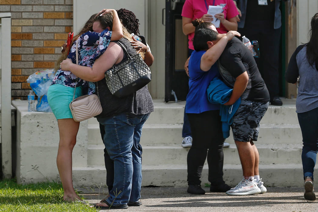 People embrace outside the Alamo Gym where students and parents wait to reunite following a shooting at Santa Fe High School Friday, May 18, 2018, in Santa Fe, Texas. ( Michael Ciaglo/Houston Chro ...
