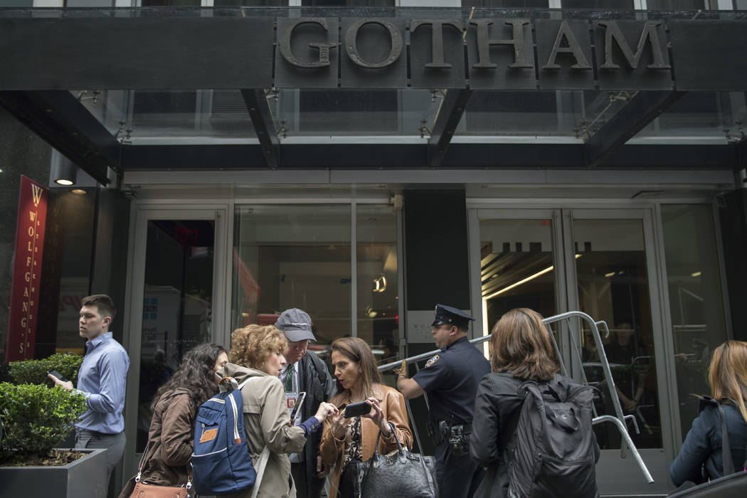 Reporters compare notes as a police officer carries a metal barricade to set up a pen for journalists outside the Gotham Hotel, Friday, May 18, 2018, in New York. Police say a woman apparently jum ...