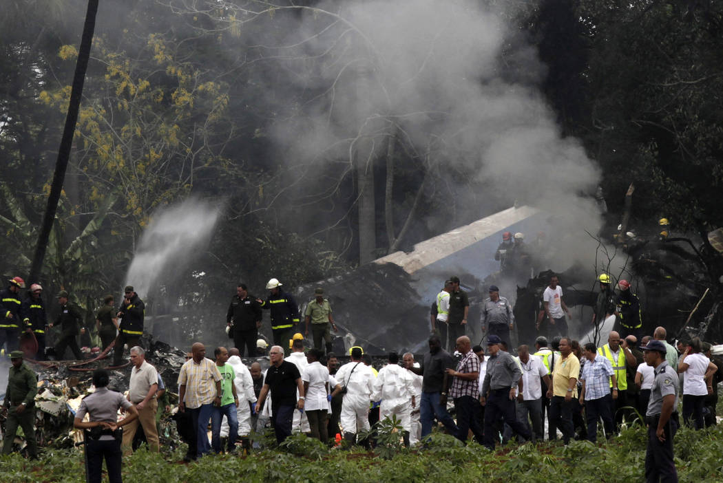 Cuba's President Miguel Diaz-Canel, third from left, walks away from the site where a Boeing 737 plummeted into a yuca field with more than 100 passengers on board, in Havana, Cuba, Friday, May 18 ...