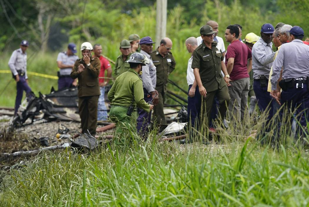 Rescue and search workers on the site where a Cuban airliner with more than 100 passengers on board plummeted into a yuca field just after takeoff from the international airport in Havana, Cuba, F ...