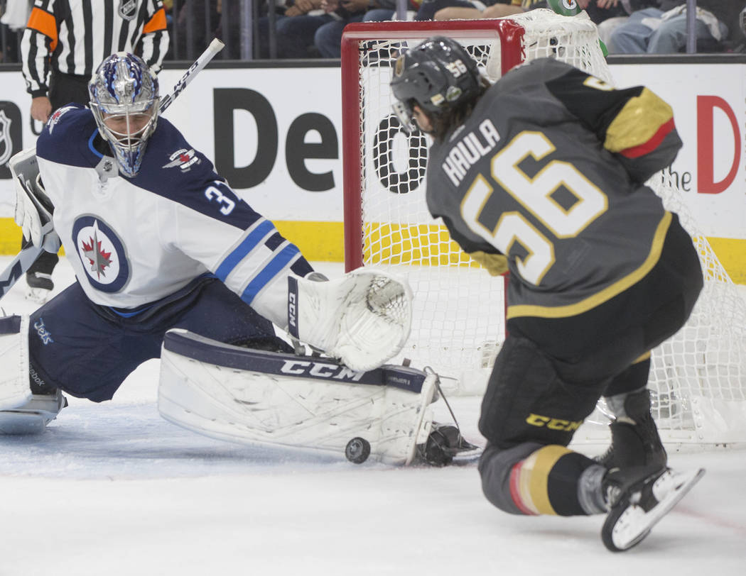 Golden Knights left wing Erik Haula (56) shoots on Jets goaltender Connor Hellebuyck (37) in the first period during game four of Las Vegas' NHL Western Conference Finals matchup with Winnipeg on ...