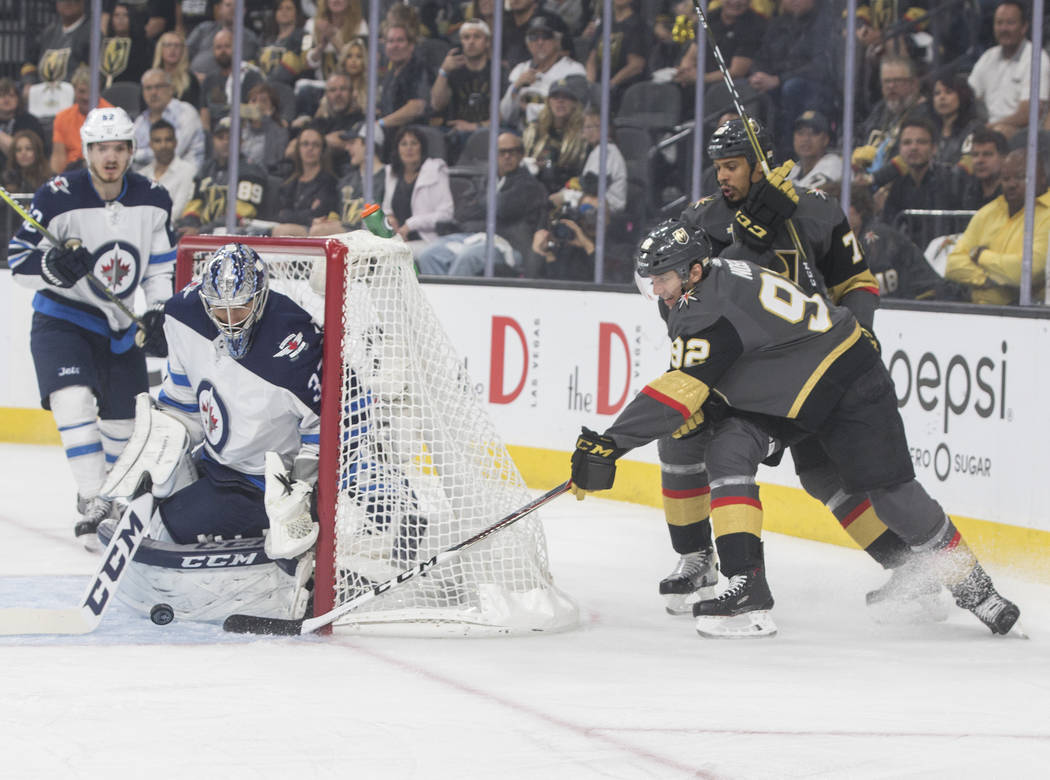 Golden Knights center Tomas Nosek (92) shoots on Jets goaltender Connor Hellebuyck (37) in the first period during game four of Las Vegas' NHL Western Conference Finals matchup with Winnipeg on Fr ...