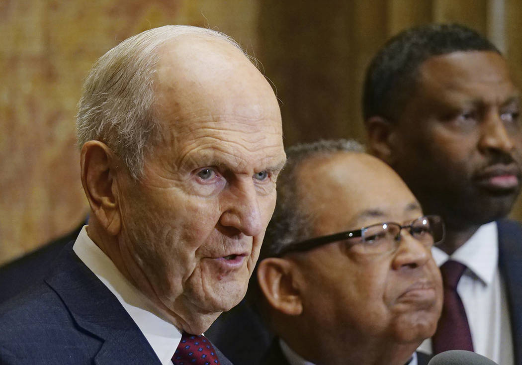 Mormon church President Russell M. Nelson, left, speaks as Leon W. Russell, chairman of the NAACP board of directors, center, and Derrick Johnson, president of the NAACP, look on during a news con ...