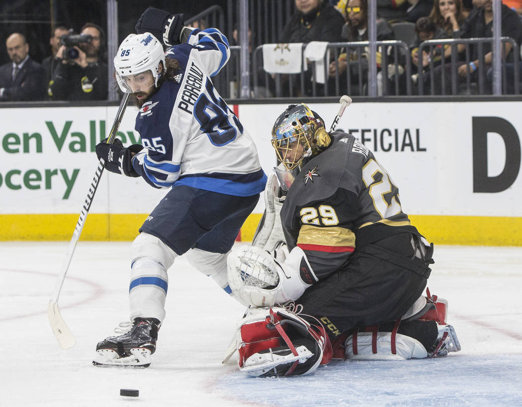 Golden Knights goaltender Marc-Andre Fleury (29) makes a save against Jets center Mathieu Perreault (85) in the second period of game four of Las Vegas' NHL Western Conference Finals matchup wit ...