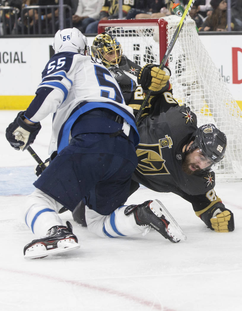 Golden Knights right wing Alex Tuch (89) collides with Jets center Mark Scheifele (55) in the second period of game four of Las Vegas' NHL Western Conference Finals matchup with Winnipeg on Friday ...