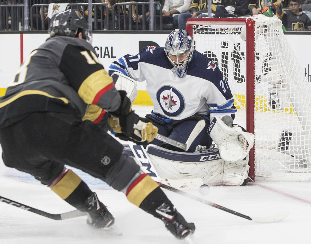 Jets goaltender Connor Hellebuyck (37) makes a save against Golden Knights left wing James Neal (18) in the third period during game four of Winnipeg's NHL Western Conference Finals matchup with ...