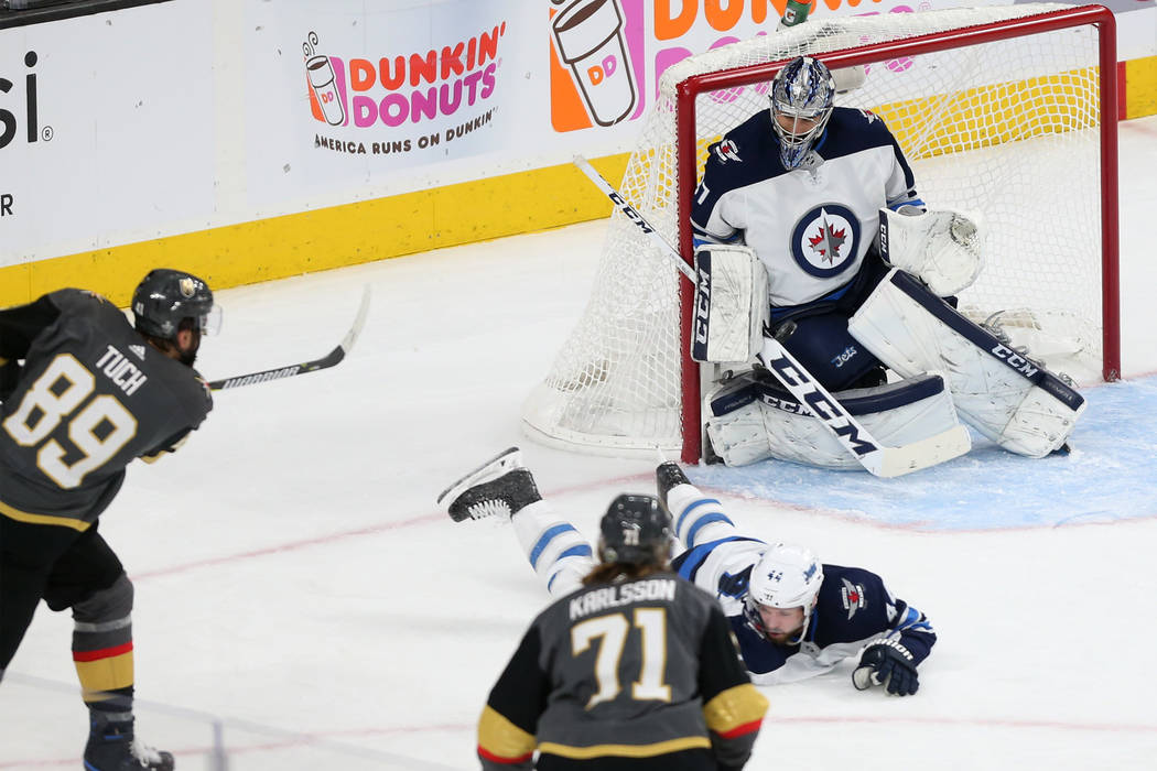 Winnipeg Jets goaltender Connor Hellebuyck (37) make a stop against Vegas Golden Knights right wing Alex Tuch (89) during the first period in Game 4 of the Western Conference Final at T-Mobile Are ...
