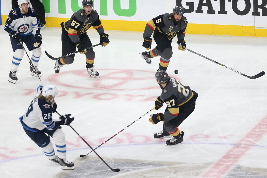 Vegas Golden Knights left wing David Perron (57), defenseman Deryk Engelland (5) and defenseman Shea Theodore (27) go for the puck against Winnipeg Jets left wing Nikolaj Ehlers (27) and right win ...