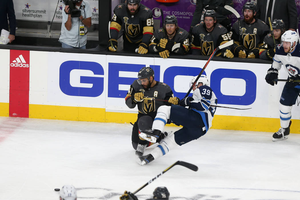 Vegas Golden Knights left wing Pierre-Edouard Bellemare (41) goes for the puck against Winnipeg Jets defenseman Toby Enstrom (39) during the third period in Game 4 of the Western Conference Final ...