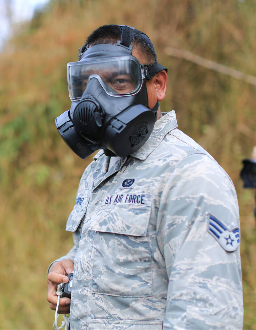 Senior Airman Orlando Corpuz, of the Hawaii Air National Guard, wears a respirator while checking sulphur dioxide levels near the Kilauea eruptions in Leilani Estates, Hawaii, on Friday, May 18, 2 ...