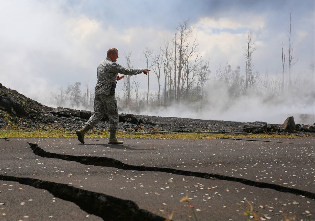 Lt. Col. Charles Anthony, of the Hawaii National Guard, walks over cracks in the road and checks sulphur dioxide levels while giving a tour of the Kilauea eruptions in Leilani Estates, Hawaii, on ...