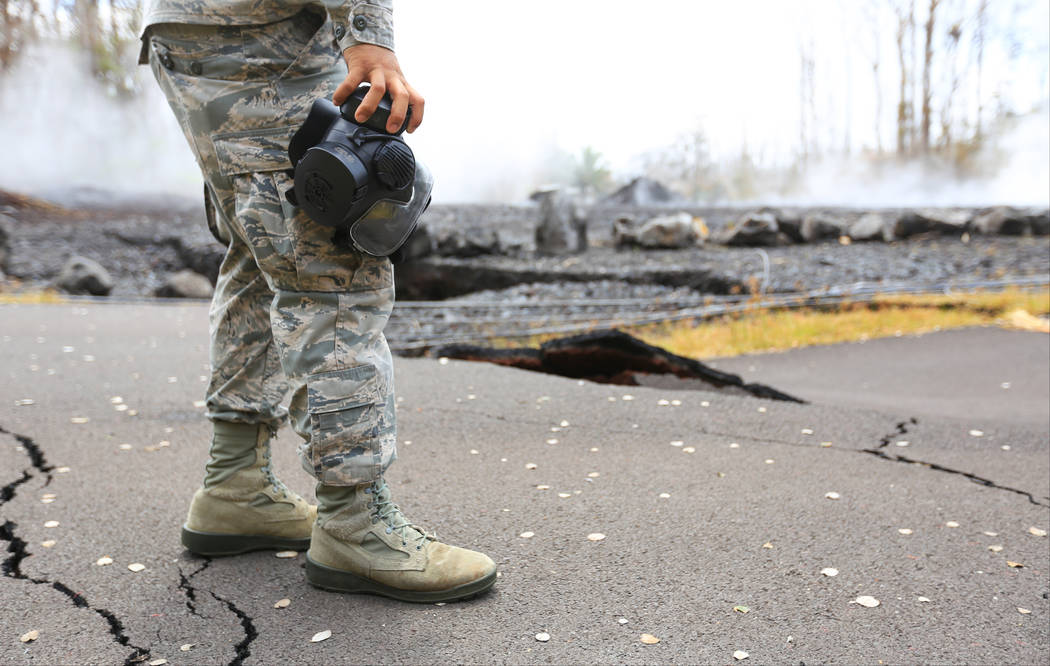 Senior Airman Orlando Corpuz carries a respirator while looking at an area affected by the Kilauea eruptions in Leilani Estates, Hawaii, on Friday, May 18, 2018. Brett LeBlanc Las Vegas Review-Journal