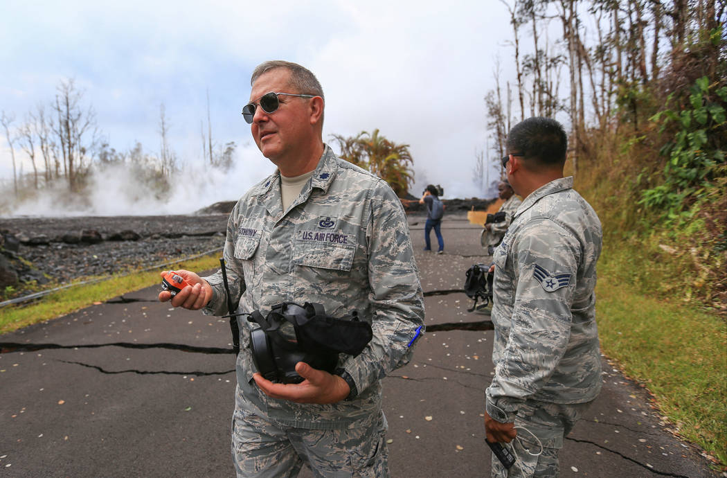 Lt. Col. Charles Anthony, left, and Senior Airman Orlando Corpuz, both of the Hawaii Air National Guard give a tour of an area affected by the Kilauea eruptions in Leilani Estates, Hawaii, on Frid ...