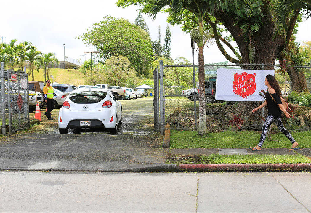 A guard checks cars as they enter a shelter in Pahoa, Hawaii, for evacuees of the Kilauea eruptions on Friday, May 18, 2018. The shelter was set up by Hawaii County Park and Recreation and staffed ...