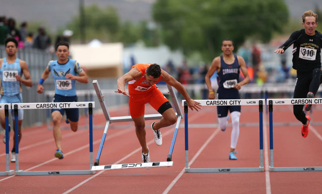Bishop Gorman's Jake Phillips crashes in the final stretch of the 4A 300 hurdles at the NIAA Track & Field Championships at Carson High in Carson City, Nev., on Friday, May 18, 2018. Ca ...