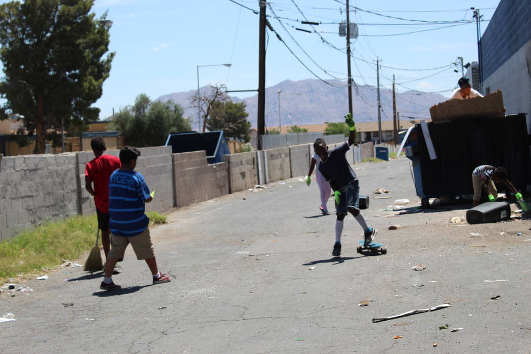 Preshay Harris, 8, plays with a skateboard on Saturday, May 19 while the Youth Helping Hands clean up an alley behind NAPA Auto Parts, 3274 Civic Center Drive, in North Las Vegas. (Max Michor/Las ...