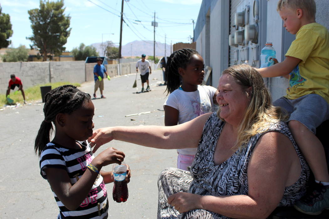 Naklya Virgil, 8, stops for a drink with Katt Smith on Saturday, May 19 while the Youth Helping Hands clean up an alley behind NAPA Auto Parts, 3274 Civic Center Drive, in North Las Vegas. (Max Mi ...