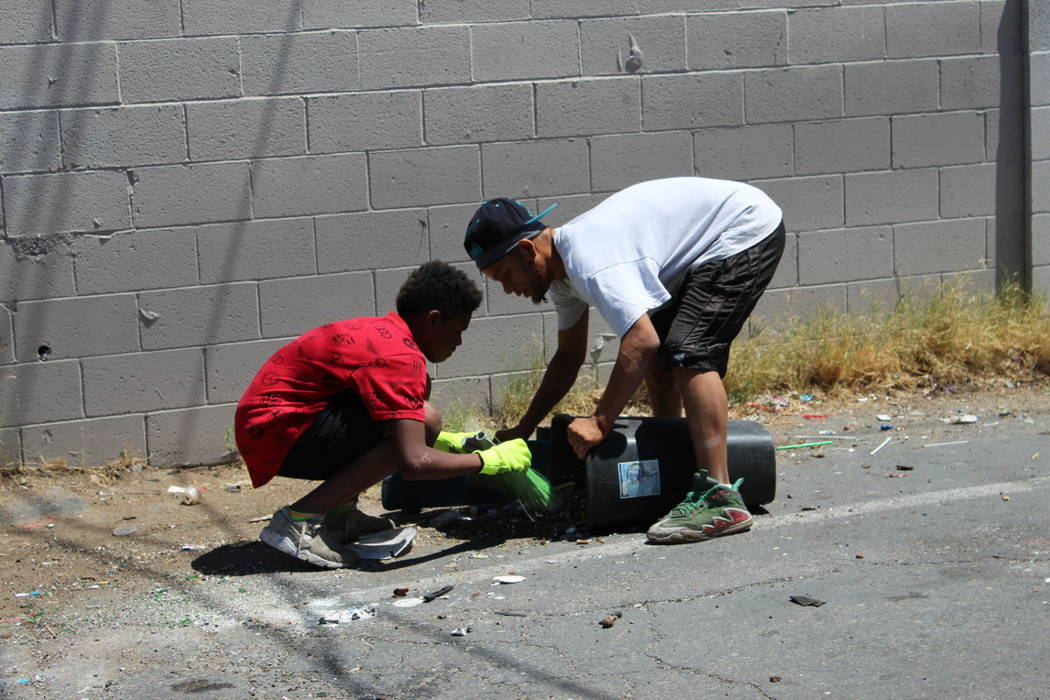 """Lee """"Turtle"""" Thompson holds a trash can while 13-year-old Joshua Bedford sweeps up trash and debris on Saturday, May 19. Joshua and the Youth Helping Hands cleaned up an alley behind NAPA Auto Par ..."""