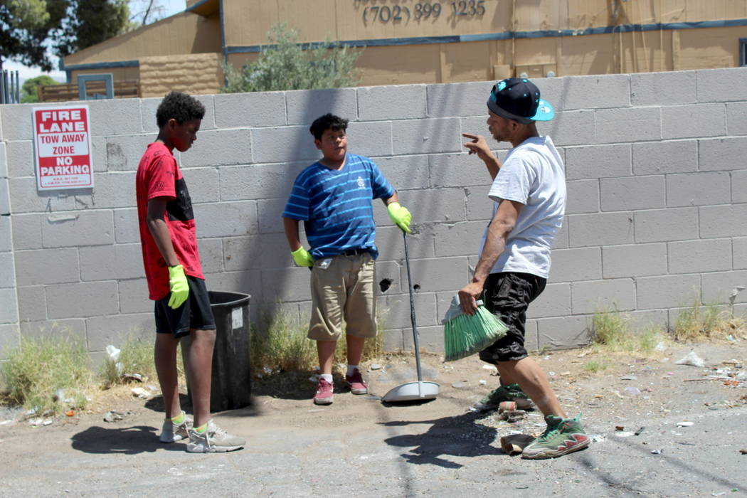 """Joshua Bedford (Left) and Martin Zamora (center), both 13, listen to Lee """"Turtle"""" Thompson on Saturday, May 19 while the Youth Helping Hands clean up an alley behind NAPA Auto Parts, 3274 Civic Ce ..."""